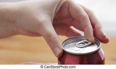 hand opening lemonade or soda drink can - unhealthy eating,...