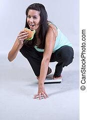 Female on weight scale eating hamburger