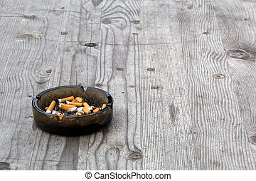An ashtray filled with smoked cigarettes on a grey wooden table