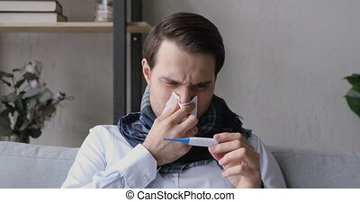 Unhealthy man blows runny nose looks at thermometer feels ...