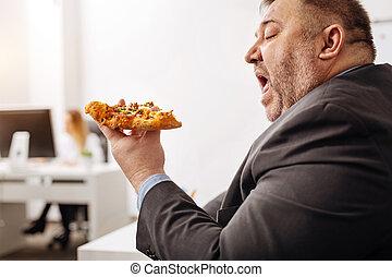 Unhealthy office worker enjoying eating junk food