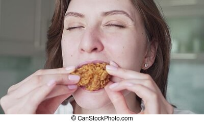 Unhealthy overeating. A woman bites chicken nuggets, close-up. Junk food slow mo