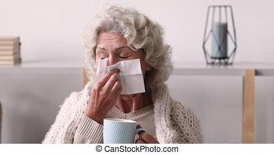 Unhealthy senior old woman using paper tissues. - Head shot ...