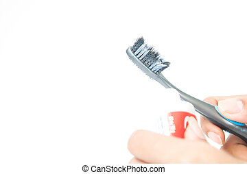 Unhealthy toothbrush on woman's hand isolated on white background
