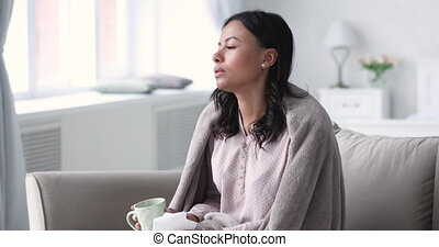 Unhealthy young african american woman sits on sofa covered in warm plaid, suffering from flu, drinking anti grippe liquid. Stressed mixed race lady caught cold, wiping runny nose, treating at home.