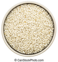 unhulled sesame seeds in a round bowl isolated on white