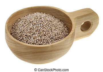 unhulled sesame seeds in a rustic wooden bowl (scoop) isolated on white