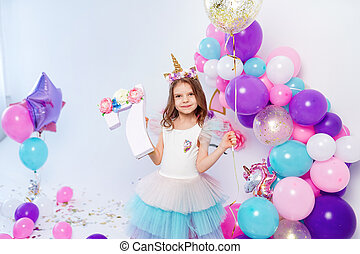 Unicorn Girl holding gold confetti air baloon and letter 7. Idea for decorating unicorn style birthday party. Unicorn decoration for festival party girl.