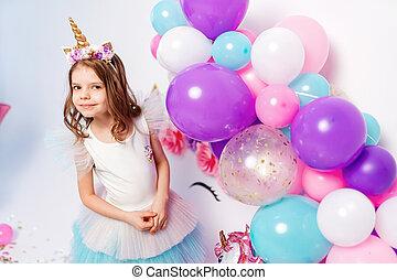 Unicorn Girl posing near air baloons. Idea for decorating unicorn style birthday party. Unicorn decoration for festival party girl.