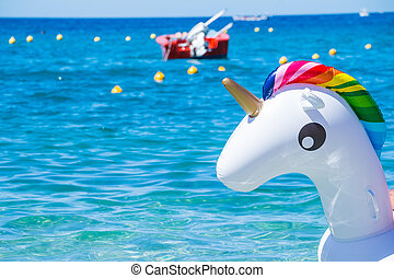 Unicorn swim tube on the beach on sea background. Inflatable rubber unicorn. Fantasy Swim Ring for Summer Pool Trip or swimming in sea, ocean, copy space