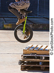 Unicycle Stunt - a unicycle rider jumping wooden pallets