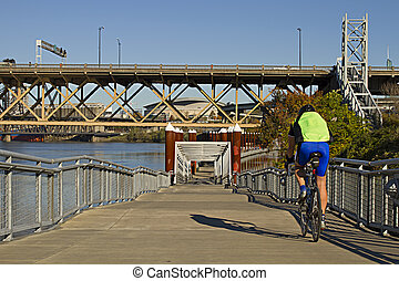 Unidentifiable Generic Cyclist Riding Bicycle along Willamette River Portland Oregon