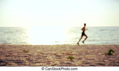 Unidentifiable man runs on beach at dawn. Defocused video. -...