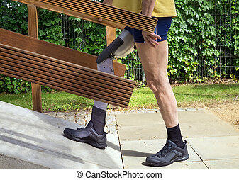 Side view on single unidentifiable man in blue shorts and yellow shirt walking up concrete ramp with prosthetic leg outdoors