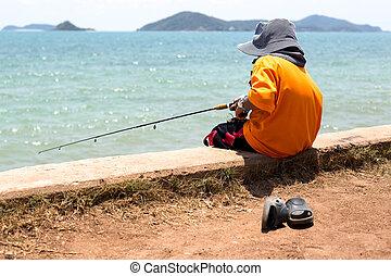 Unidentified boy is fishing in the sea