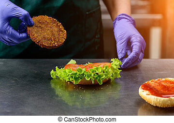 Unidentified chef preparing veggie burger with yummy vegetable