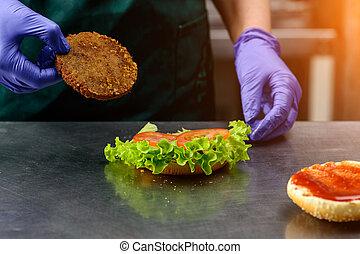 Unidentified chef preparing veggie burger with yummy vegetable