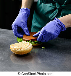 Unidentified chef preparing veggie burger with yummy vegetable p