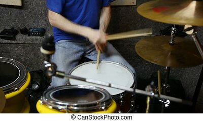 unidentified drummer playing on dums in studio -...