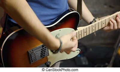 unidentified guitarist playing on electric guitar in studio