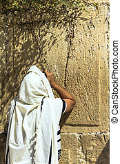 Unidentified jewish worshiper in tallith praying at the Wailing Wall an important jewish religious site