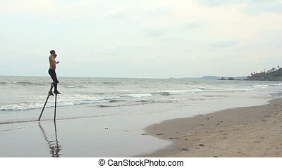 Unidentified man dancing on the stilts. - Goa, India -...