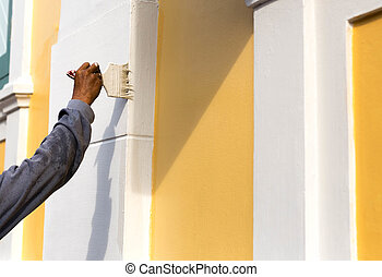 Unidentified man painting with brush on the building wall