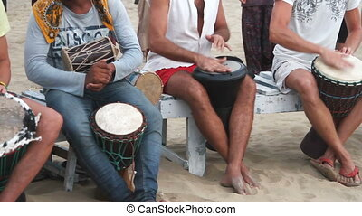Unidentified man playing on drum at the beach.