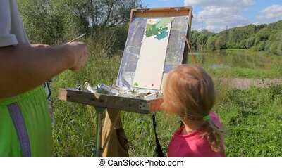 unidentified man teaching girl to painting summer nature -...