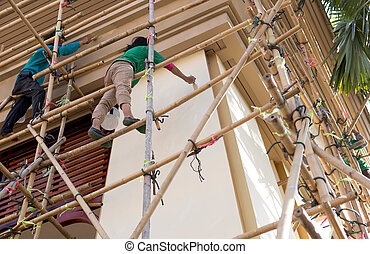 Unidentified painter on  scaffolding doing renovate for architecture wall