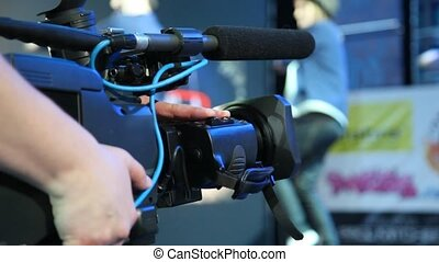 unidentified video operator with camera recording modern...