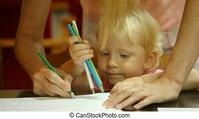 unidentified woman with little girl drawing pencils on white paper