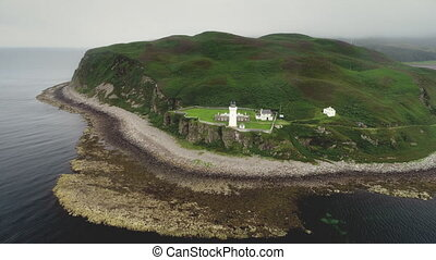 Uninhabited island Davaar aerial birds eye view. Greenery summer landscape in gloomy weather on shore of small Scottish island in Gulf of Atlantic Ocean Firth of Clyde. Dramatic cinema shot in 4K, UHD