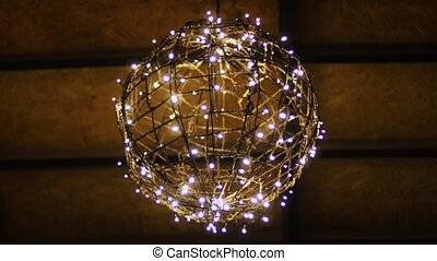 Unique, homemade light fixture, made from a string of white LED lights, strung over a wire frame globe and hung from the ceiling.
