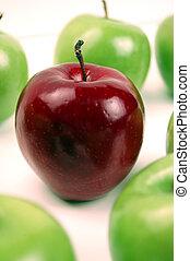 Uniqueness - Dark Red - A dark red apple stands alone amidst...