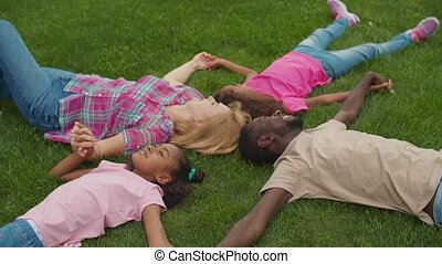 United family holding hands lying on lawn in circle