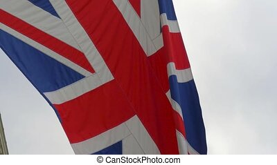 United Kingdom Flag waving on wind in blue sky.