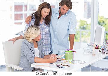 United smiling team of interior designer at desk in bright...
