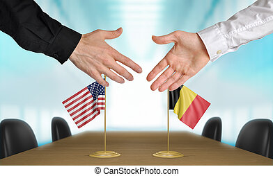 United States and Belgium diplomats shaking hands to agree deal