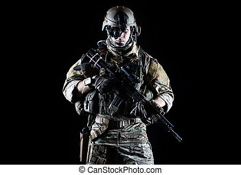 United States Army ranger with assault rifle on dark...