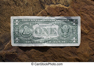 A single US dollar sits on a rock