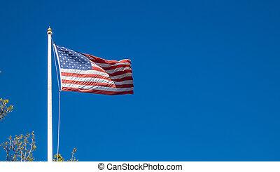 United States flag on a pole waving on blue sky background.