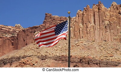 United States Flag waving against huge mountains