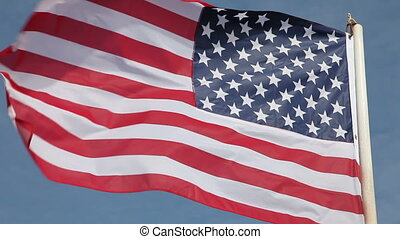 United States flag waving in wind against clear blue sky