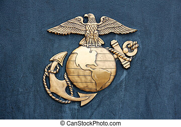 Insignia of the United States Marine Corps in golden burnished metal on a dark blue-gray wall.