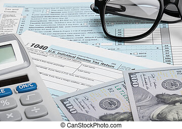 Tax Form 1040 with calculator, dollars and glasses
