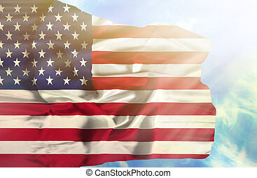 United States of America waving flag against blue sky with sunrays