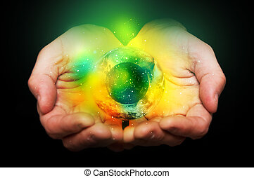 Universe in hands - Hands holding a glowing yellow and green...