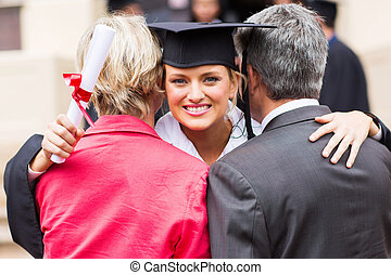 university female graduate hugging parents