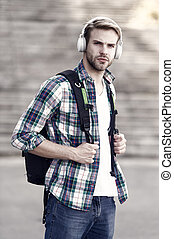 university student headset and backpack. Online education. Audio book concept. guy study in university. student e learning. school life. Listen music. Modern and digital youth. trendy man